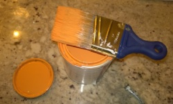 orange paint can and brush on counter