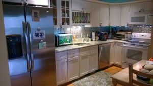kitchen tin backsplash stainless fridge dishwasher rug table string lights