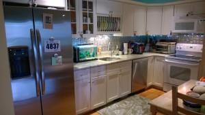 kitchen tin backsplash stainless fridge dishwasher rug table string lights