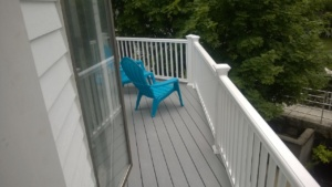 blue plastic adirondack chairs on deck
