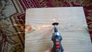 using a dremmel tool to cut a notch into a stripped screw as sparks fly