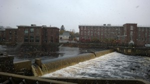 view of the ipswich river, waterfall / dam, and ebsco, while it's snowing