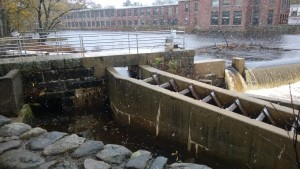 view of the ipswich river, waterfall / dam, and fish ladder, while it's snowing