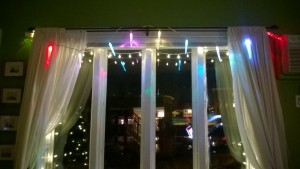 multi colored LED icicle lights hanging in living room window