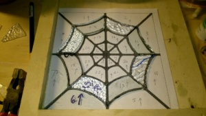 working on stained glass spiderweb in the basement workshop cage