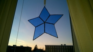 blue stained glass star hanging in living room window