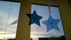 blue and teal stained glass stars hanging in living room window