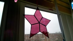 raspberry stained glass star hanging in living room window