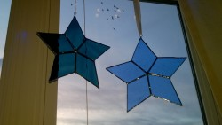 diy stained glass stars hanging in living room window with birds flying by