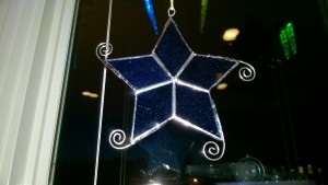 blue stained glass snowflake star hanging in living room window