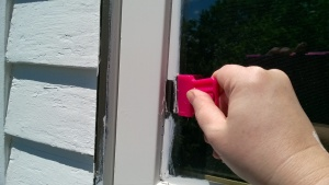 using a razor blade to scrape the excess paint off the glass