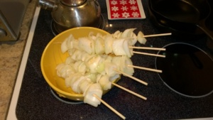 skewering the seasoned onions to prepare them for grilling