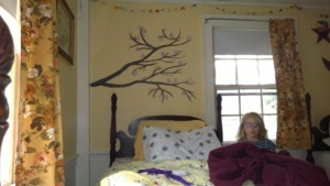 meara standing in front of the cherry blossom branch i painted on her wall